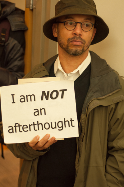 Emory English professor Dr. Lawrence Jackson holds a sign in silent protest.