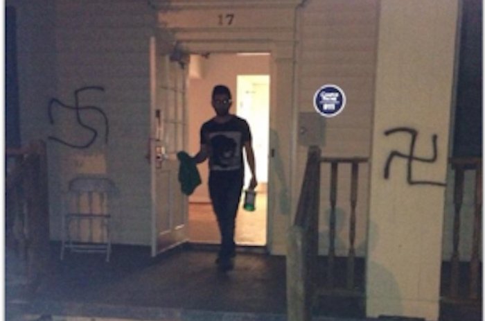 College sophomore Jake Mor is pictured trying to remove swastikas that were spray painted on the Alpha Epsilon Pi (AEPi) fraternity house on Sunday morning. Photo Courtesy of Emory AEPi.