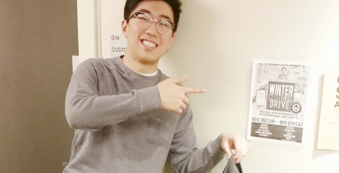 College sophomore Alvin Choi proudly donates a piece of clothing for AKPsi's clothing drive. As service committee chair, Choi hopes that the fraternity's effort will make a change in the community. | Photo by Loli Lucaciu